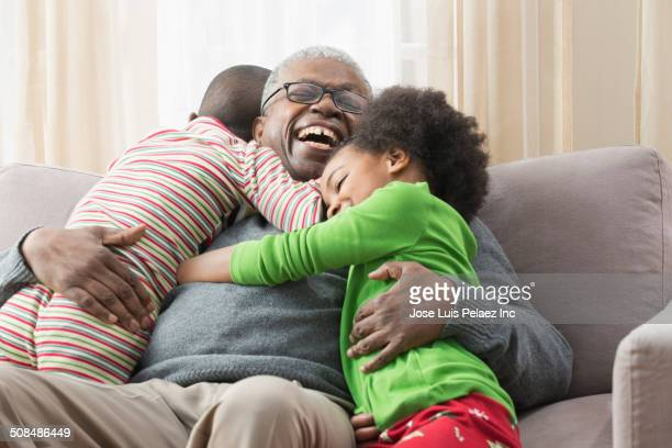 older man hugging grandchildren on sofa - african american family home stock photos and pictures