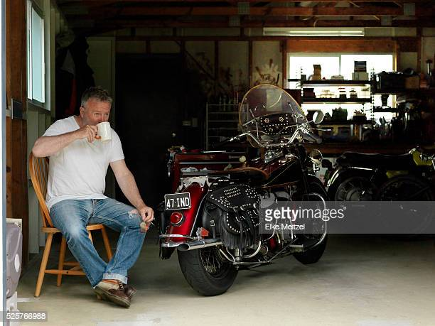 older man inside garage with motor bikes