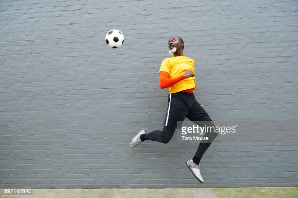 older man kicking football - kicking stock pictures, royalty-free photos & images
