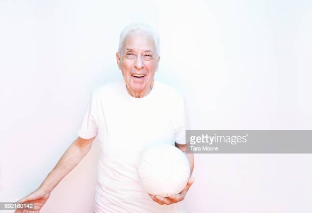 older man laughing with ball - tee sports equipment stock pictures, royalty-free photos & images