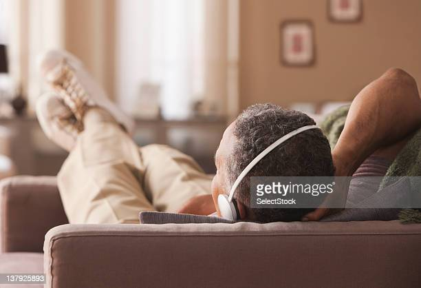 Older man laying on couch with headphones
