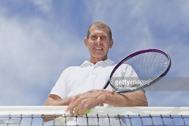 Older man leaning on tennis net