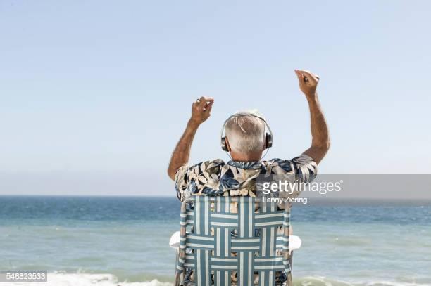 Older man listening to headphones on beach