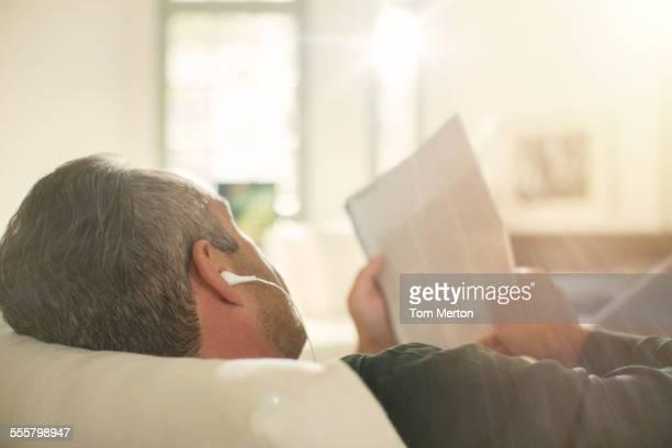 Older man listening to headphones on sofa