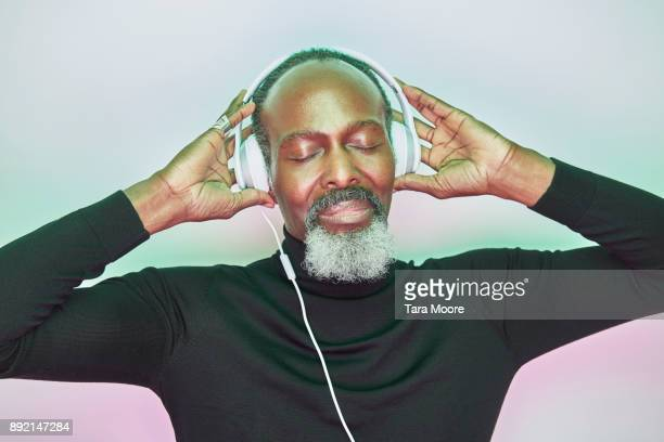 older man listening to music with headphones