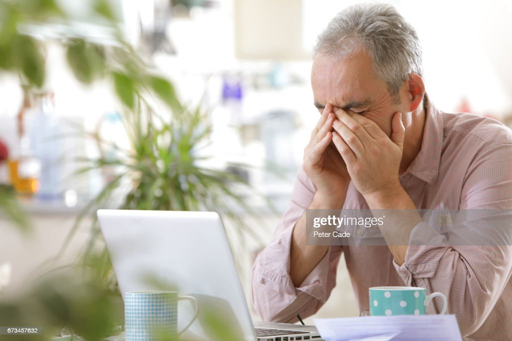 Older man looking stressed with laptop : Stock Photo