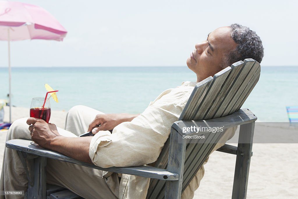 Marvelous Older Man Lounging On Beach Chair With Beverage High Res Ocoug Best Dining Table And Chair Ideas Images Ocougorg