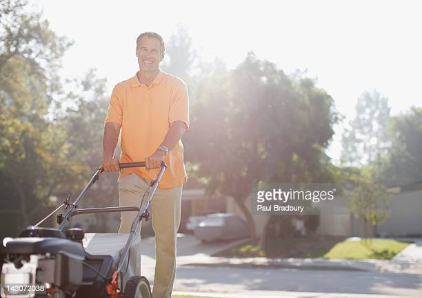 Older man mowing front lawn