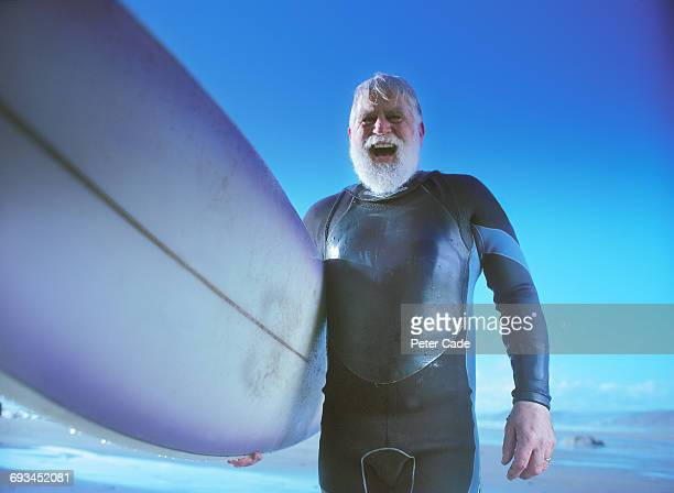 older man on beach holding surfboard - senior men stock pictures, royalty-free photos & images