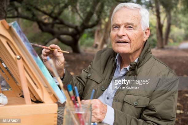 Older man painting in park