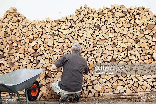 Older man piling wood into wheelbarrow