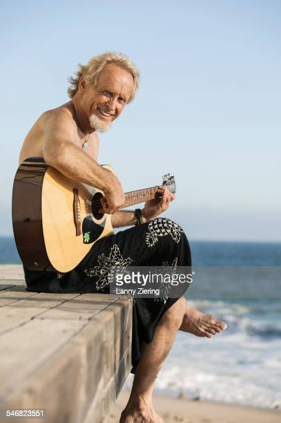 Older man playing guitar on pier over beach