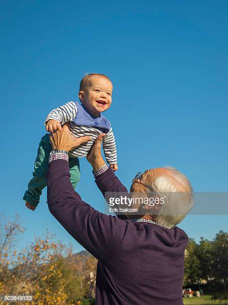 Older man playing with grandson outdoors