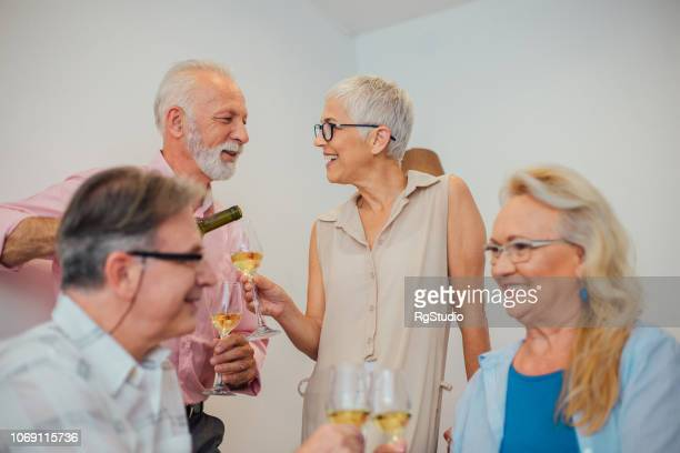 older man pouring wine to his guests - drunk wife at party stock pictures, royalty-free photos & images