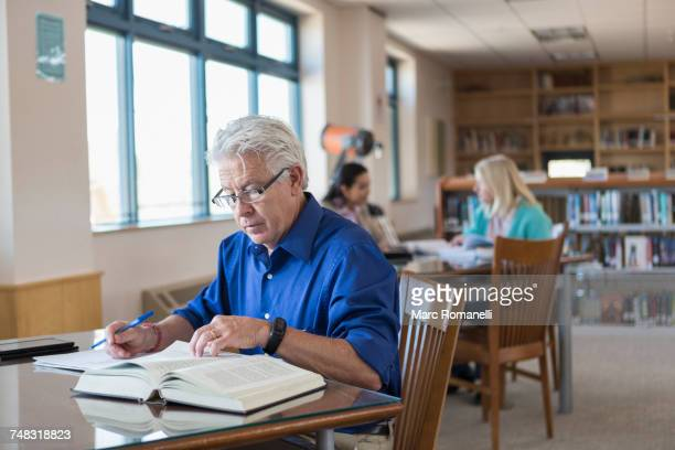 older man reading book in library and writing notes - old university stock pictures, royalty-free photos & images