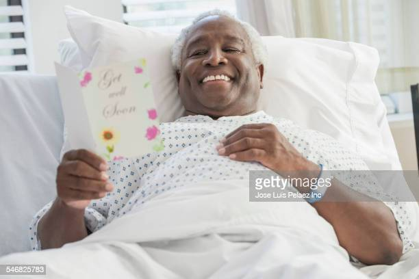Older man reading get well soon card in hospital bed