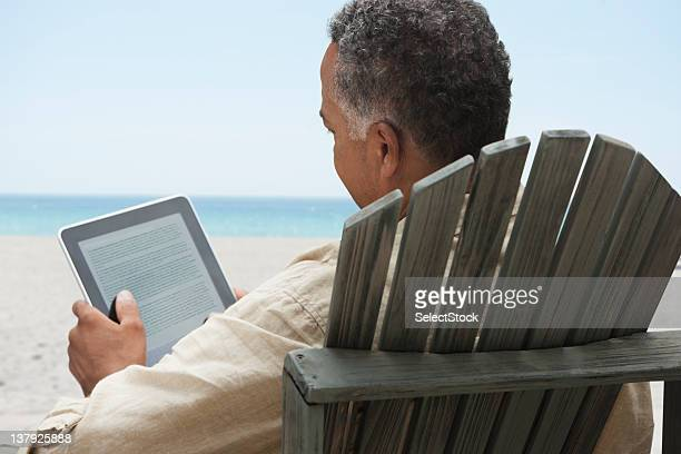 Older man reading on electronic tablet