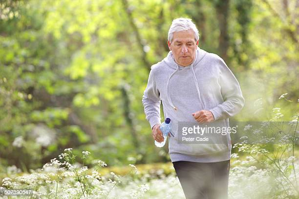 older man running through woodland and flowers - cardiovascular exercise stock pictures, royalty-free photos & images
