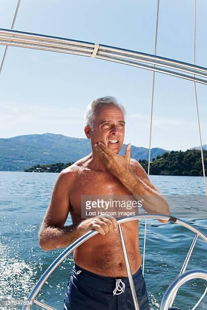 ältere mann segeln auf dem see - halbbekleidet stock-fotos und bilder