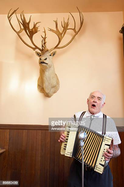 Older man singing with accordian with deer head