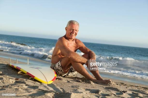 Older man sitting near surfboard on beach