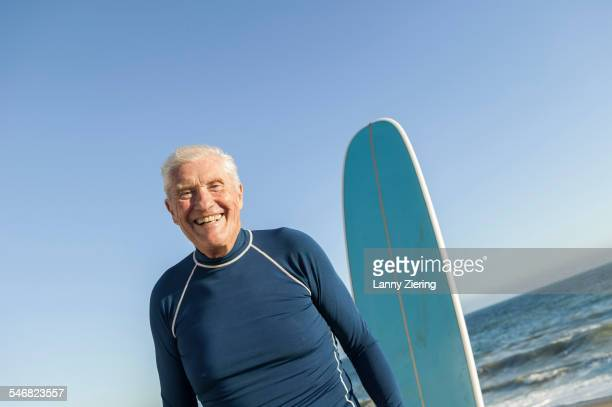 Older man standing near surfboard on beach