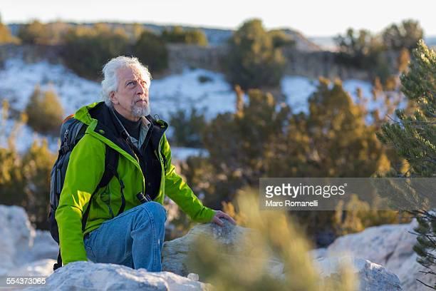 Older man standing on rock formations