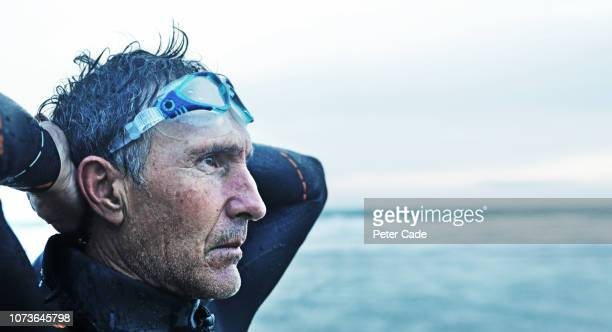 older man stood on beach after swimming in the sea - looking away stock pictures, royalty-free photos & images