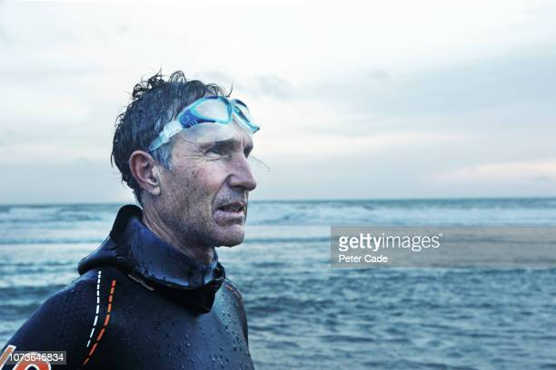 older man stood on beach after swimming in the sea - image focus technique stock pictures, royalty-free photos & images