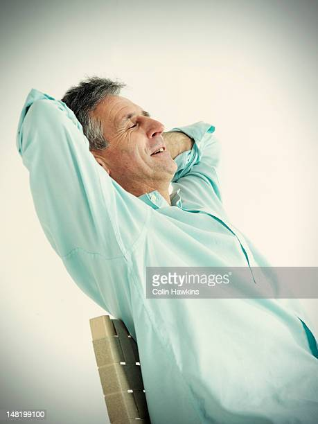 Older man stretching in chair
