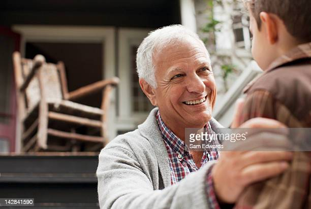 Older man talking to grandson outdoors