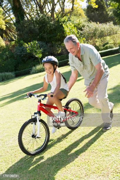 Ältere Mann Lehren Enkelin zu reiten Fahrrad