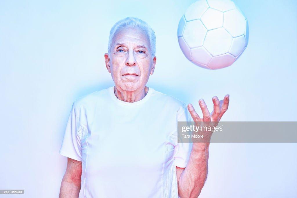older man throwing up ball : Stock Photo