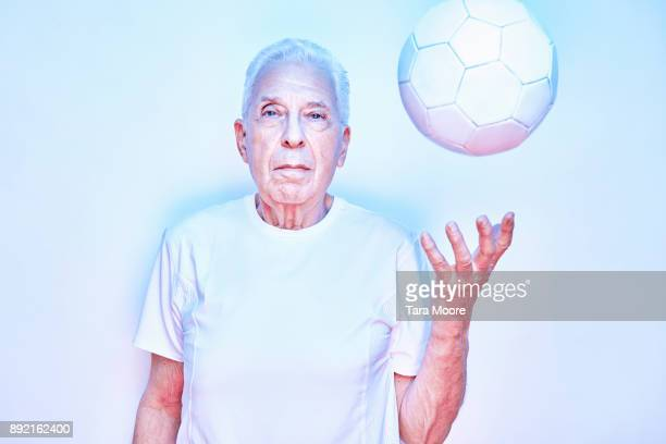 older man throwing up ball
