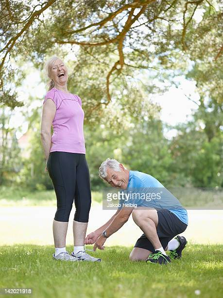 older man tying wifes shoelaces - lace fastener stock pictures, royalty-free photos & images