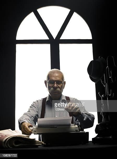 Ältere Mann Schreiben an Schreibmaschine am Schreibtisch und Zeitungen