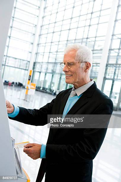 older man using boarding computer - munich airport stock photos and pictures