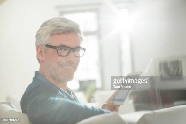 Older man using digital tablet on living room sofa