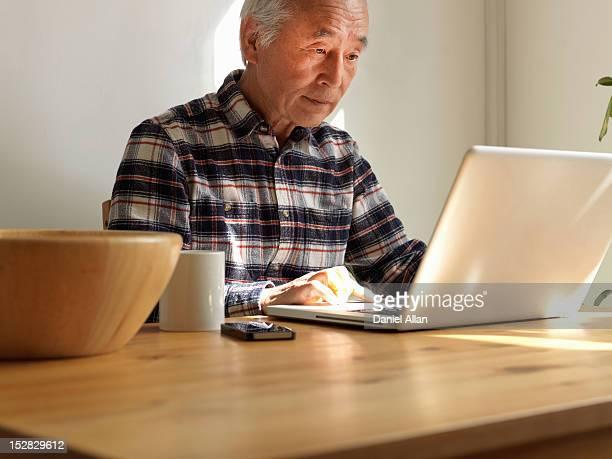 Older man using laptop at table