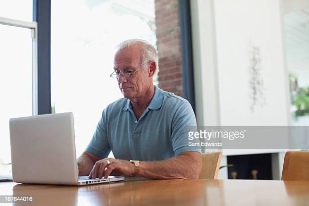 Older man using laptop indoors