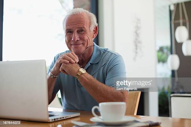 älterer mann mit laptop im innenbereich - 65 69 jahre stock-fotos und bilder