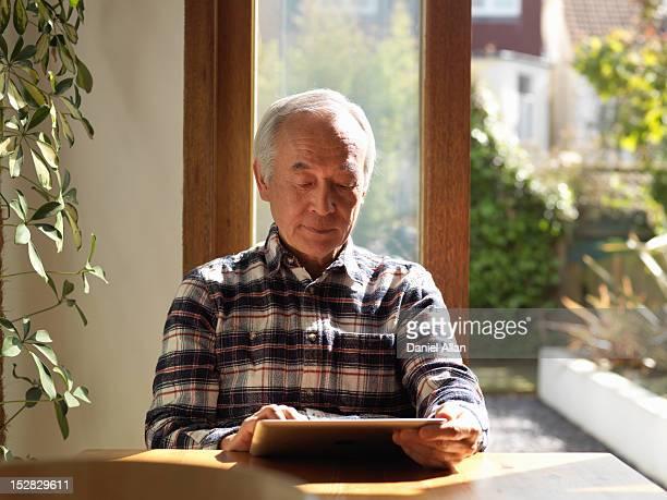 古い男性のタブレットコンピューターを使用してテーブル
