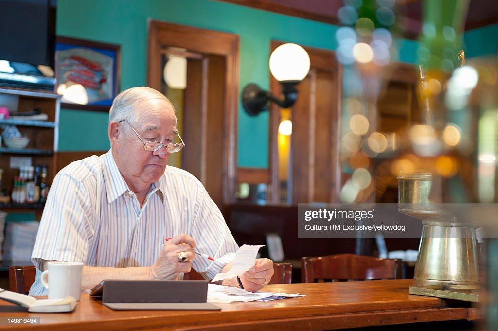 Older man using tablet computer in cafe : ストックフォト