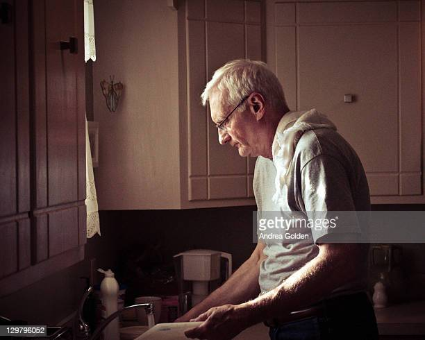 Older man washing dishes