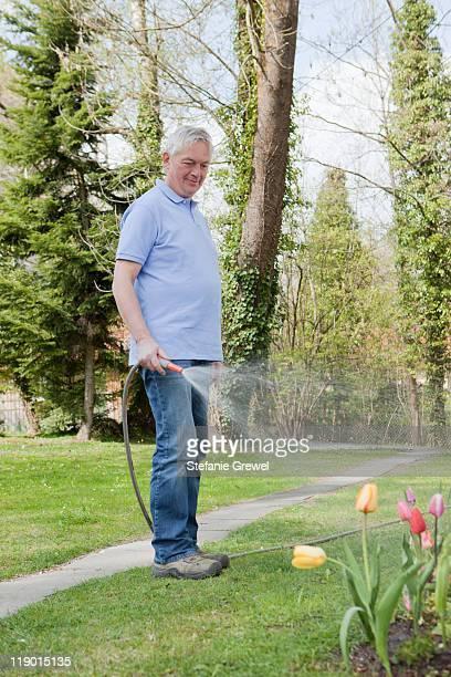 older man watering flowers in backyard - stefanie grewel stock-fotos und bilder