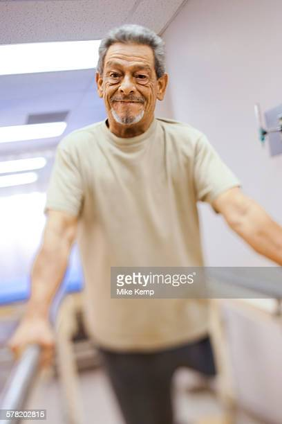 Older man with one leg exercising and smiling