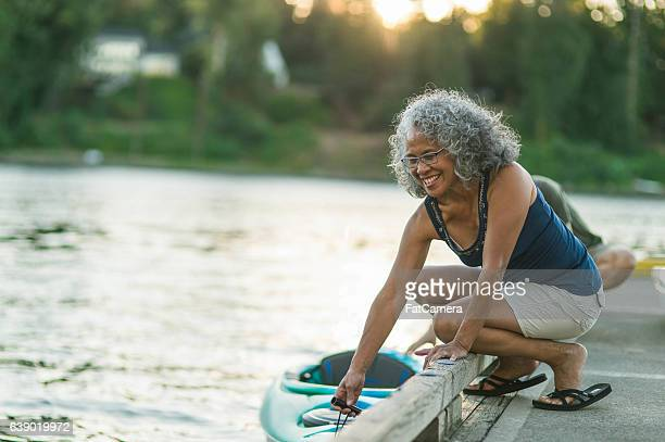 Older mature couple putting kayak in the water together