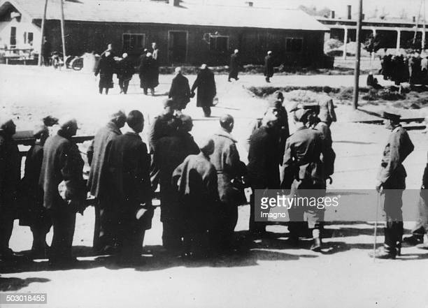 Older men are led by the SS men directly to the crematorium. Ca. 1943. Photograph. .
