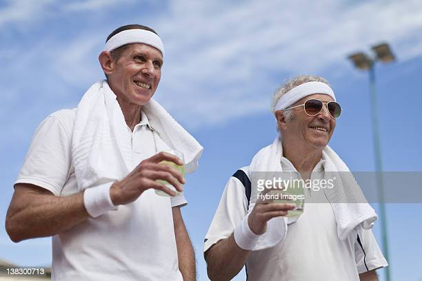 older men drinking lemonade outdoors - doubles stock photos and pictures
