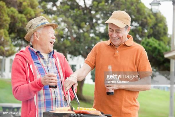 Older men grilling food together outdoors